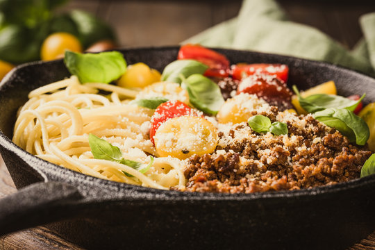 Delicious spaghetti Bolognaise or Bolognese with savory minced beef and cherry tomatoes garnished with parmesan cheese and basil in cost iron pan. Healthy italian food. Retro style toned.