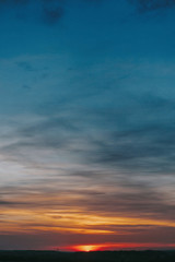 Sunset. Amazing beautiful sunset or sunrise on sky with clouds in yellow, pink and blue colors. Dawn or dusk. Nature wallpaper.