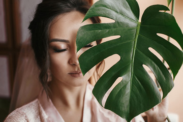 gorgeous bride portrait with monstera leaf. beautiful woman getting ready for wedding, holding green leaf and posing. skin care and make-up. sensual moment