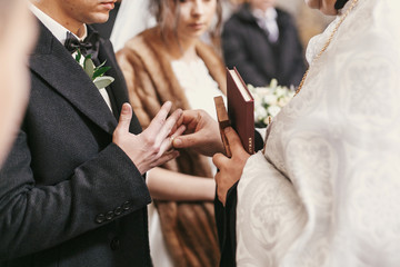 priest putting on wedding rings on bride and groom hands during holy matrimony in church.