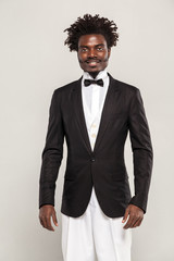 Richly african gentelman with afro hair style in classic style tuxedo and bow tie smiling. Indoor, isolated studio shot on gray background