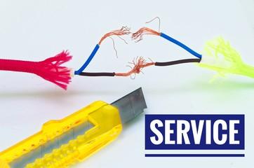 Bunte Kabel die getrennt und notdürftig geflickt wurden und einem Cuttermesser mit Aufschrift Service