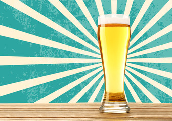 Glass of beer on wooden table against patterned background