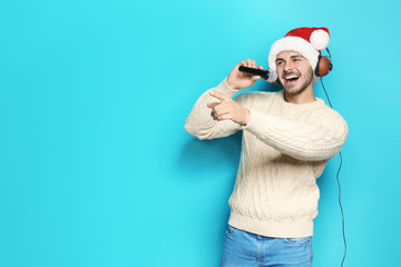 Young man in Santa hat singing into microphone on color background. Christmas music