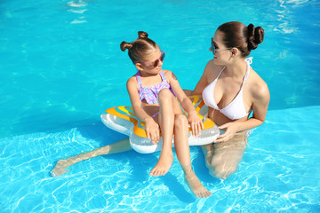 Young mother with little daughter in swimming pool on sunny day