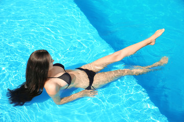Beautiful young woman wearing bikini in blue swimming pool