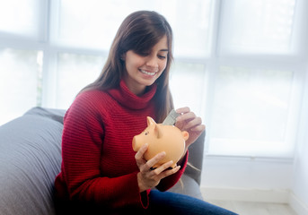 Woman entering money in a piggy bank at home