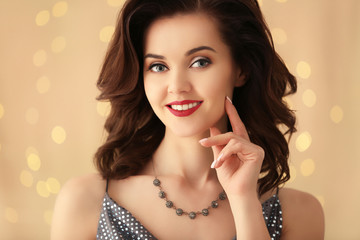 Portrait of beautiful young woman with luxury jewelry on light background