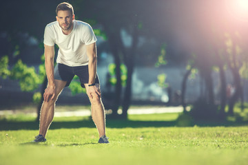 Full length portrait of focused sportsman training in park. He is bending forward and putting hands on knees with concentration. Copy space in right side