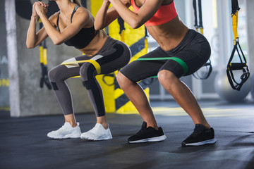 Close up of athletic women in squat together in gym. Couple of fit girls are exercising with resistance band for lower body relief. They are wearing sport clothes and sneakers