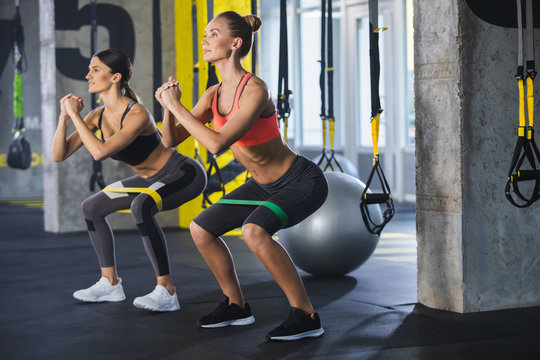 Two smiling athletic girls are squatting synchronously with outfit in fitness studio. Women are enjoying leg and buttocks work out with resistance band. Training together with friend in gym concept