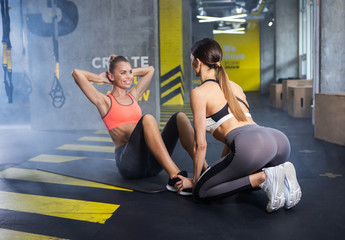 Smiling woman is exercising stomach muscles while her mate is helping her. Cheerful lady is sitting on mat and doing abdominal crunches while other female is holding her feet for easing process