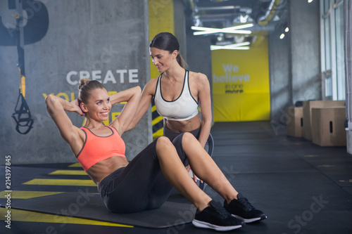 4e4757940ec Happy sporty woman is doing abdominal crunches in gym. She is enjoying work  out with personal assistant. Smiling female trainer is sitting near girl  while ...
