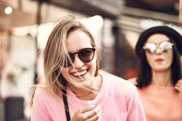 66cae3710b Portrait of beaming woman wearing sunglasses while looking at camera.  Cheerful comrade situating near her