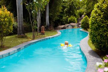 Baby in swimming pool. Kids swim aid.