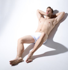 Sexy man in underwear. Muscular male model in trendy white underwear. Handsome sexy muscular naked man lying on white background. Male swimwear and underwear concept.