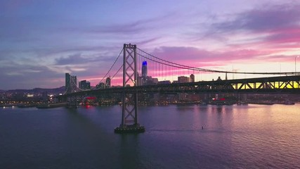 Fototapete - Aerial cityscape flythrough video of the Bay Bridge and San Francisco skyline with colorful sunset