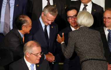 U.S. Secretary of the Treasury Mnuchin kisses IMF Managing Director Lagarde and shakes hands with World Bank president Kim as they arrive for the official photo at the G20 Meeting of Finance Ministers in Buenos Aires