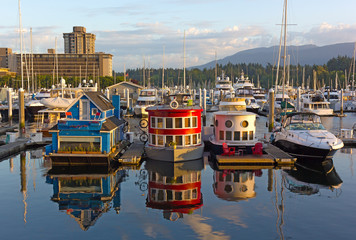 Fototapete - Boat houses on the water of Coal Harbour Marina at sunrise. City panorama with floating boathouses, forest, and mountain ridges on the horizon.