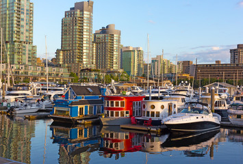 Fototapete - Coal Harbour waterfront and beautiful boat houses with reflection at sunrise. A city view from a walkway along the marina in summer.