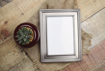Silver frame mockup with aloe plant  in the small glass vase. Empty frame mock up for presentation artwork. Template framing for modern art.