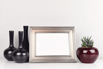 Blank silver frame, on a white table with aloe and vases. Mockup with copy space