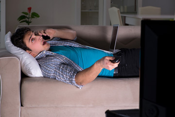 Man watching tv late at night