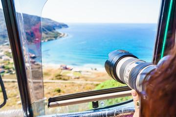 Tourist taking photo with camera on seacoast Greece