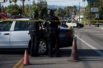 Police officers block the street near a Trader Joe's store where a hostage situation unfolded in Los Angeles