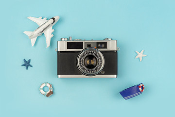 Retro camera with toy plane on pastel blue background