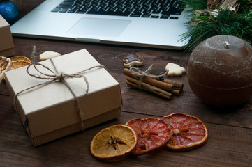 Christmas working place, Christmas gift boxes, dry oranges, cinnamon and ginger cookies on brown wooden table with computer.
