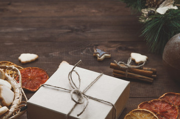 Top  view  of Christmas background. Christmas presents,cookies and dry oranges on a brown wooden table.Toned image.