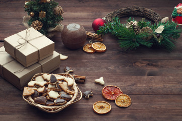 Top  view  of Christmas background. Christmas presents,cookies and dry oranges on a brown wooden table.