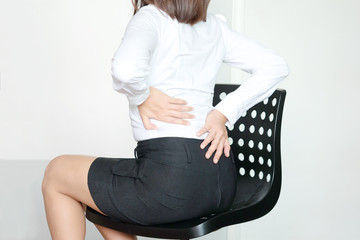 young woman sitting have back pain and sore waist concept of pain relief and health care