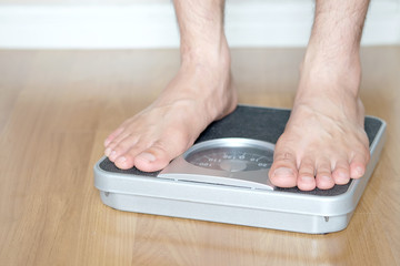 Legs of men standing on scales weight. Concept of health and weight loss.