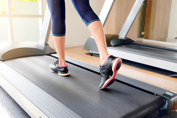leg of woman running exercise  on treadmill in the gym which runner athletic by running shoes. Health and sport concept background,
