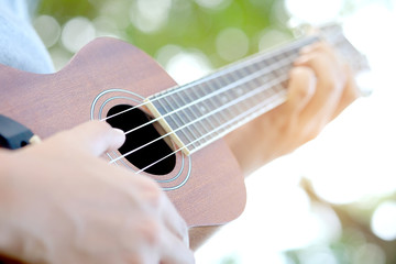 Woman's hand Play Guitar ukulele  Natural bokeh background