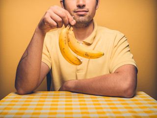 Young man against yellow with bananas