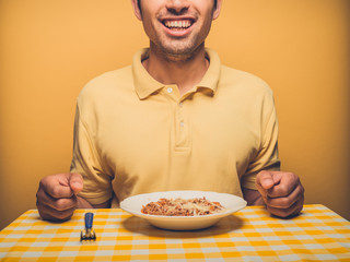 Young man against yellow eating mince