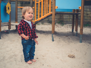 Cute little toddler standing in the sand at playground
