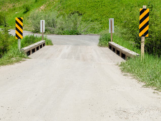 rural dirt road crossing small bridge with yellow and black caution signs along a lush green hillside