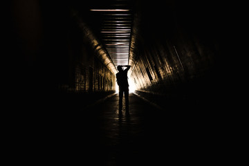 The silhouette of the photographer shooting light at the end of the tunnel.