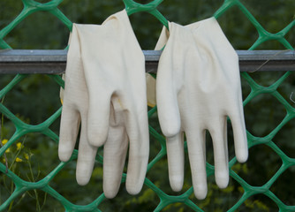 A pair of protective gloves for working in the garden, turned inside out, dried on the grate