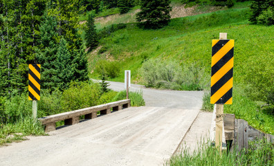 rural dirt road crossing small bridge with yellow and black caution signs along a lush green forest hillside