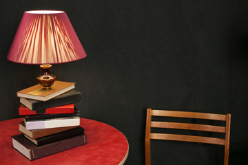 art floor lamp made of books stands on a red round table against a black wall next to the back of a wooden chair