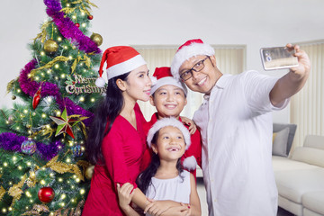 Asian family taking picture near Christmas tree