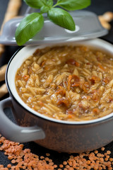 Close-up of italian soup with red lentils and pasta in a pot, selective focus
