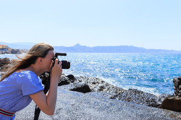 Woman photographer Nature photographer shooting the sea. Travel Concept