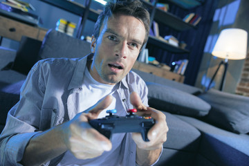 Pleasurable entertainment. Handsome nice good looking man holding a game console and looking at the screen while being involved in the game