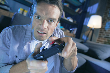I will win. Serious determined handsome man holding a game console and playing a video game while wanting to win